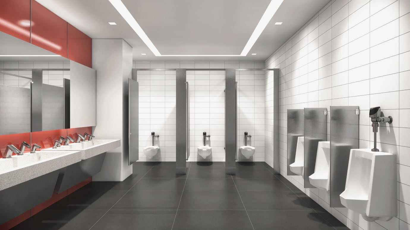 Wide angle view of public restroom with sensor faucets and flushometers installed