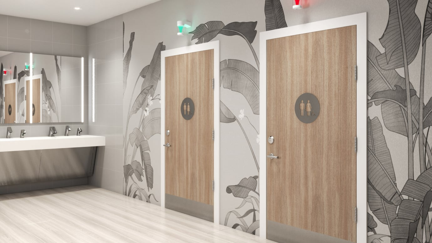 Photo of two doors with handicap accessible signs on them, sensor faucets in view
