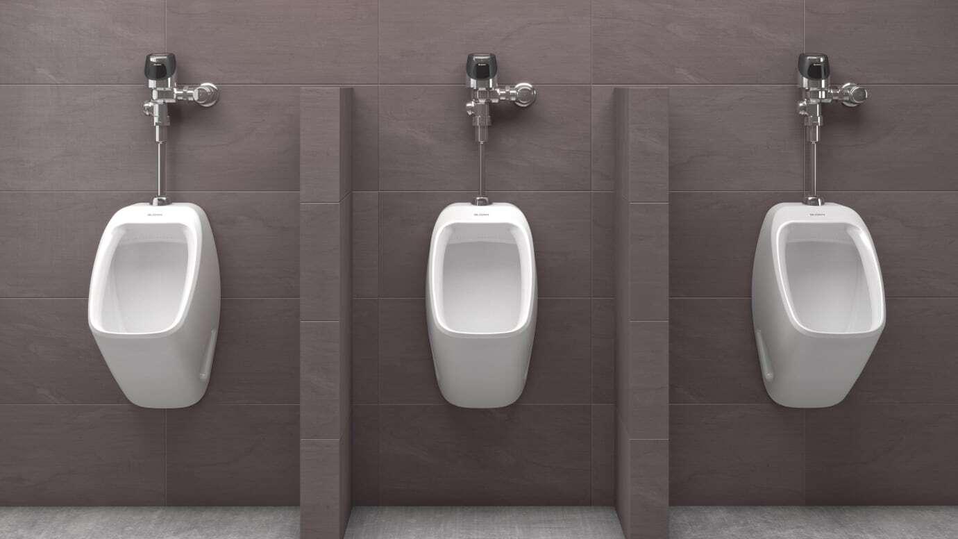 Focused shot of three sensor flushometer urinal combos in a restroom