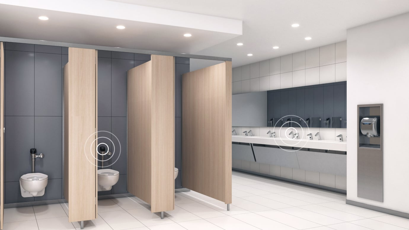 View of public restroom with sensor faucet and flushometers installed