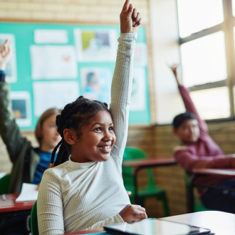 坐在课桌边上举手的孩子