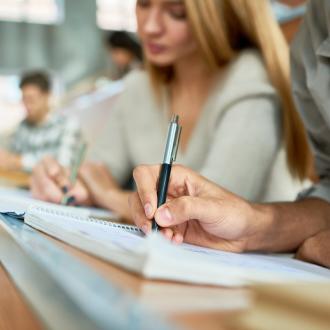 手握钢笔在笔记本上写东西