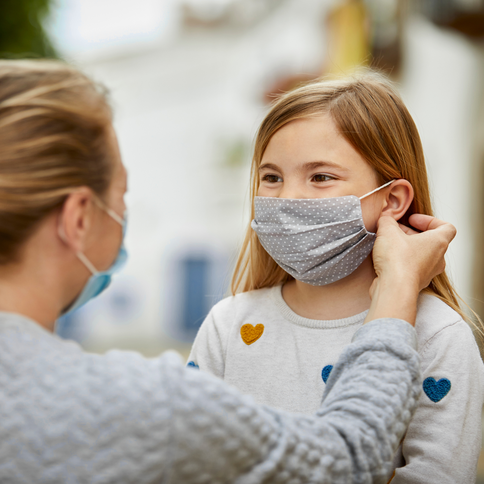 正在帮助孩子戴口罩的人